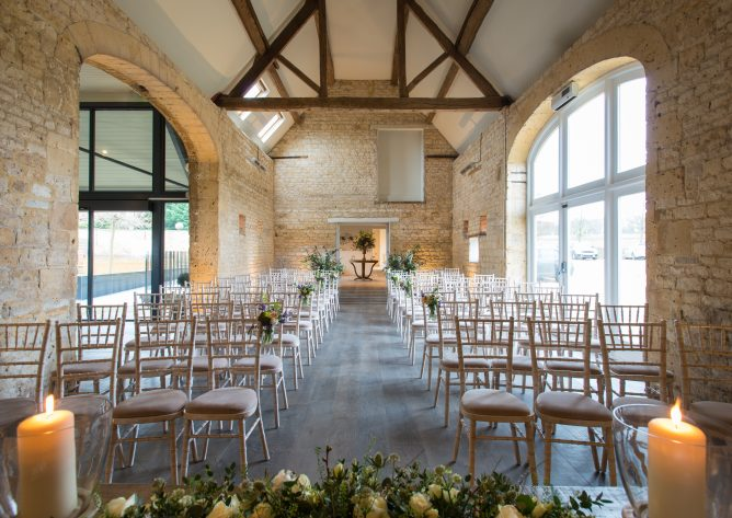 Interior of our Cotswold wedding venue, looking west down the aisle in Stone Barn