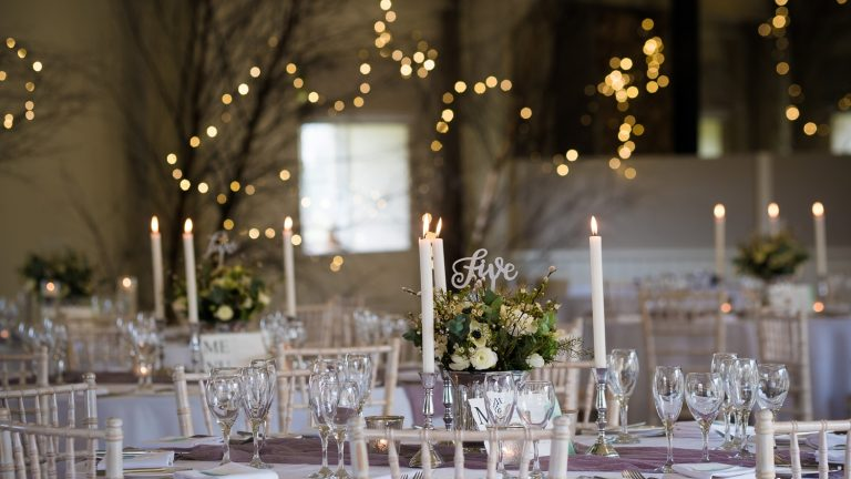 Round tables laid with pretty candles and table decorations