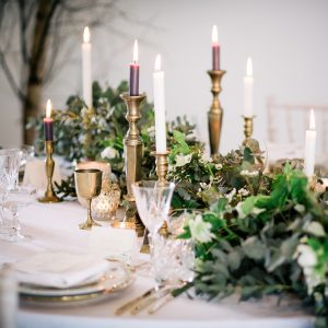 Gold goblets and candlesticks with green floral table decorations