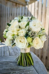 Hand tied bridal bouquet in whites and soft neutrals, perfect for a barn wedding venue