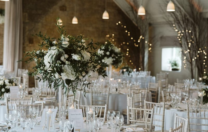 Tall vases of flowers decorate the dining tables. Photography by David Hughes Photography