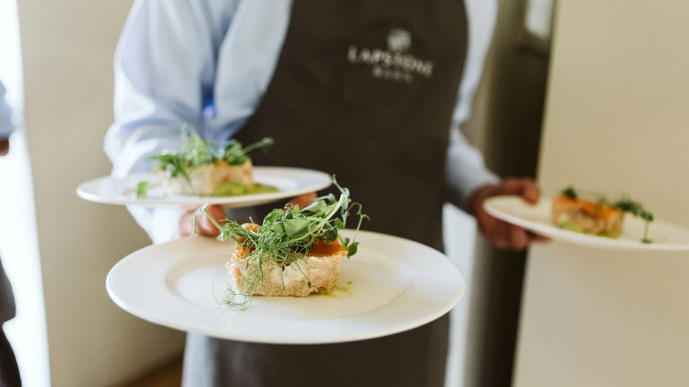 Waiter carrying plates of food to guests