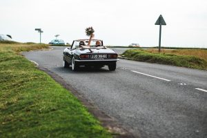 Bride and groom leaving their wedding in the Cotswolds by car
