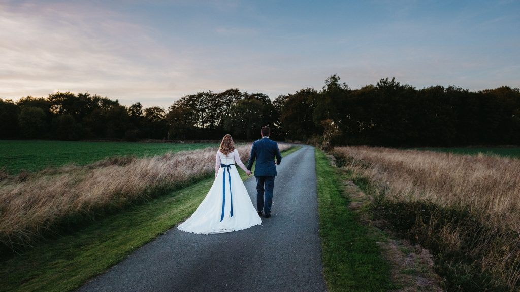 Bride and groom walking down the drive together. Image by Tanli Joy Photography