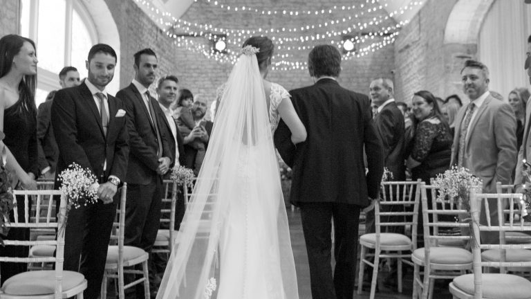 Fairy light canopy overhead as the bride walks down the aisle