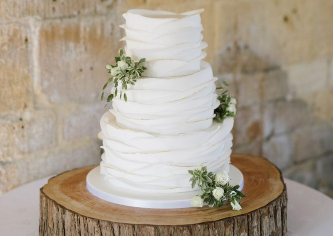 Wedding cake displayed on a log slice stand