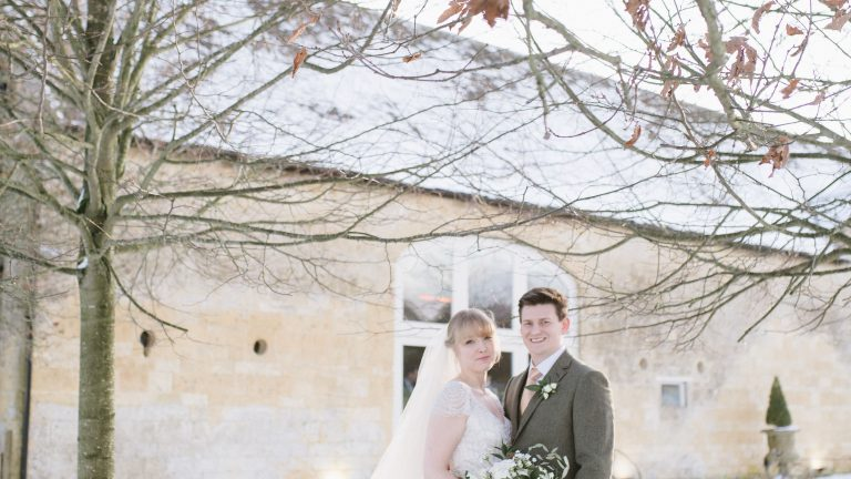 Bride and groom standing in front of the Cotswold stone barn in the snow on their wedding day