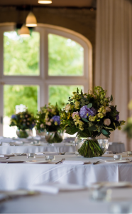 Tables laid for the wedding breakfast with floral arrangements by The Broadway Florist