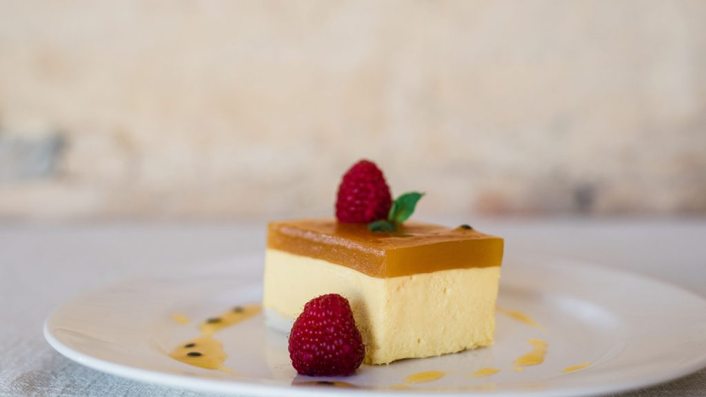 Mango & Passion Fruit Cheesecake served on a white plate
