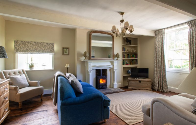 The comfortable sitting room with sofas, armchairs and beautiful fireplace