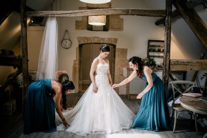 Bride and bridesmaids making final preparations in the Hayloft