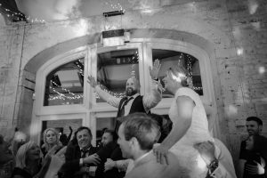 Bride and groom on friend's shoulders on the dance floor