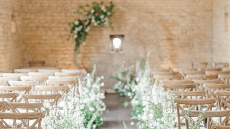 The barn set for a wedding ceremony with floral meadow along the aisle