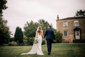 Bride and groom walking hand and hand in the garden