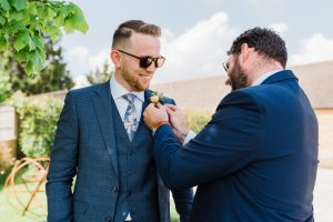 Groomsmen helping the groom put on his buttonhole