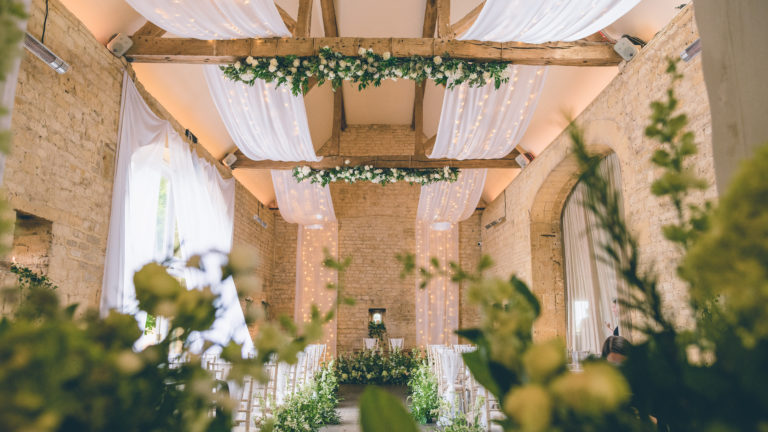 Cotswold barn dressed for a wedding ceremony with drapes and hanging flowers