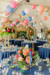 Colourful paper lanterns hanging over round tables decorated with bright neon colours