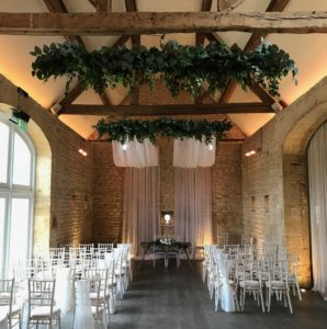 Drapes and foliage decorating the wedding ceremony space