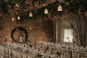 Floral bars hanging over the rows of tables laid for the wedding breakfast
