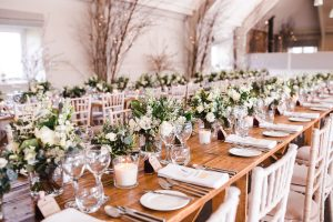 Floral arrangements and place settings at the wedding breakfast