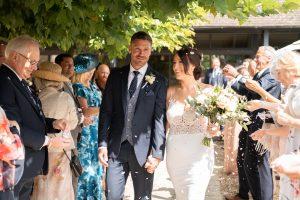 Bride and groom hand in hand after outdoor wedding ceremony